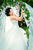 Beautiful elegant asian bride stands under the wedding arch. Wedding dress and accessories. Wedding