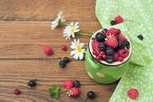 Pottery jar with berries on wooden background