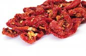 a pile of sun-dried tomatoes on a white background