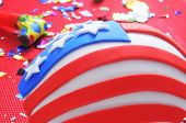 a cupcake decorated as the United States flag on a table with a red tablecloth with a party horn and