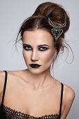 Young beautiful woman with stylish gothic make-up and hairdo