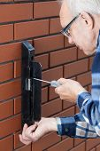 Senior Man Repairing Gate Lock