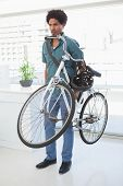 Handsome businessman standing with his bike in his office