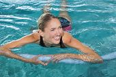 stock photo of health center  - Fit blonde swimming with foam roller in swimming pool at the leisure centre - JPG