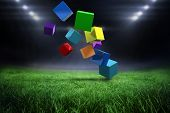 3d colourful cubes floating against football pitch with bright lights