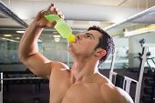 Close-up of a sporty young man drinking energy drink in gym