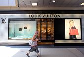 SANTA MONICA, CALIFORNIA - TUES. JUNE 24, 2014: A woman walks past a Louis Vuitton store in Santa Mo