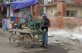 Man With Sugar Cane Pressing Machine Mounted On A Cart.