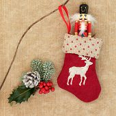Christmas stocking and toy soldier drummer decoration, holly, snow covered fir and pine cone over br