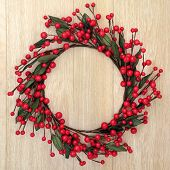 Red bauble christmas wreath over oak background.