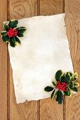 Christmas blank parchment letter with variegated holly over oak wood background.