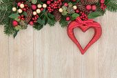 Christmas background border with red heart decoration, holly, baubles, mistletoe and winter greenery