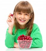 Cute girl is eating cherries, isolated over white