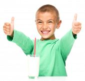 Cute boy with glass of milk is showing thumb up sign using both hands, isolated over white