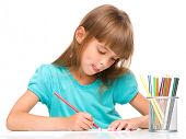 Little girl is drawing using color pencils while sitting at table and sticking her tongue out, isola