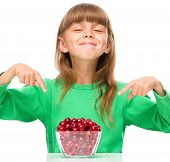 Cute girl is pointing to the bowl full of cherries, isolated over white