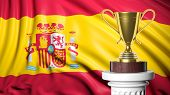 Golden trophy with Spanish flag in background