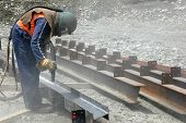 pic of friction  - tradesman sandblasting steel beams for building project - JPG
