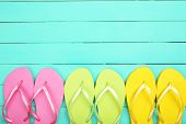 Bright flip flops on wooden background