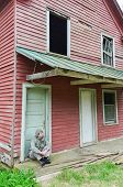 The depressed man sits in front of an abandoned house