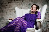 Fashion glamour girl dreamily sitting in white chair in violet lace dress