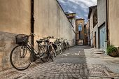picture of porphyry  - italian narrow street in the decadent old town - bicycles in a grunge dark alley in Italy