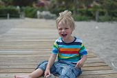 Flashy boy sits on a wooden walkway on the beach