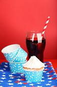 American patriotic holiday cupcake and glass of cola on red background