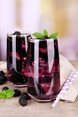 Tasty cool blackberry lemonade with ice on wooden table, on light background