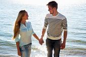 Young couple walking on beach together in love holding around each other.