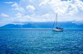 Sailboat under a blue sky with fluffy white clouds.