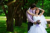 Wedding shot of bride and groom embracing  in park