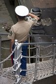 NEW YORK - MAY 22: A U.S. Marine salutes the American Flag before disembarking the amphibious dock landing ship USS Oak Hill (LSD 51) moored at Pier 92 for Fleet Week NY on May 22, 2014.