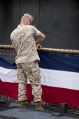 NEW YORK - MAY 22: A sailor fastens bunting to the railing on the amphibious dock landing ship USS Oak Hill (LSD 51) moored at Pier 92 for Fleet Week NY on May 22, 2014.