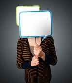 Young lady standing and holding an empty speech bubble in front of her head