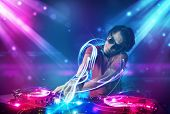 Young energetic Dj mixing music with powerful light effects