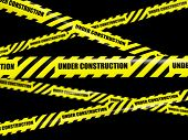 Under construction concept background - yellow warning caution ribbon tape on black background