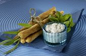Sticks with feta cheese tied with string blue background white dip herbs
