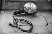 Black and white image of an old portable spotlight with its coiled electrical cord lying abandoned o