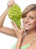 portrait of attractive  caucasian smiling woman isolated on white studio shot eating grapes