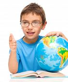 Little boy is holding globe while sitting at table, isolated over white