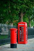 Red telephone and post box in street with historical architecture in London.