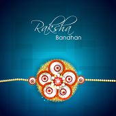 Beautiful floral decorated rakhi on abstract blue background for Happy Raksha Bandhan celebrations.