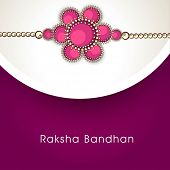 Beautiful rakhi on grey and purple background for Happy Raksha Bandhan celebrations.