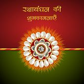Beautiful rakhi on red and green background for Happy Raksha Bandhan celebrations.