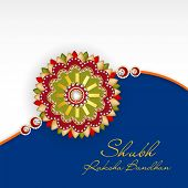 Beautiful rakhi on grey and blue background for the occasion of Happy Raksha Bandhan celebrations.