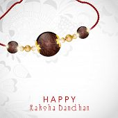 Beautiful rakhi on floral decorated grey background for Happy Raksha Bandhan celebrations.