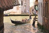 Gondolier Sails With Tourists Sitting In A Gondola, Venice, Italy