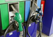 pic of gasoline station  - Several Gasoline Pump Nozzles With White Paper At Petrol Station - JPG