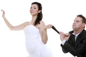 stock photo of male-domination  - Emancipation idea concept. Humorous funny wedding couple bride and groom - woman pulling the tie of a man trying to show her domination isolated ** Note: Soft Focus at 100%, best at smaller sizes - JPG